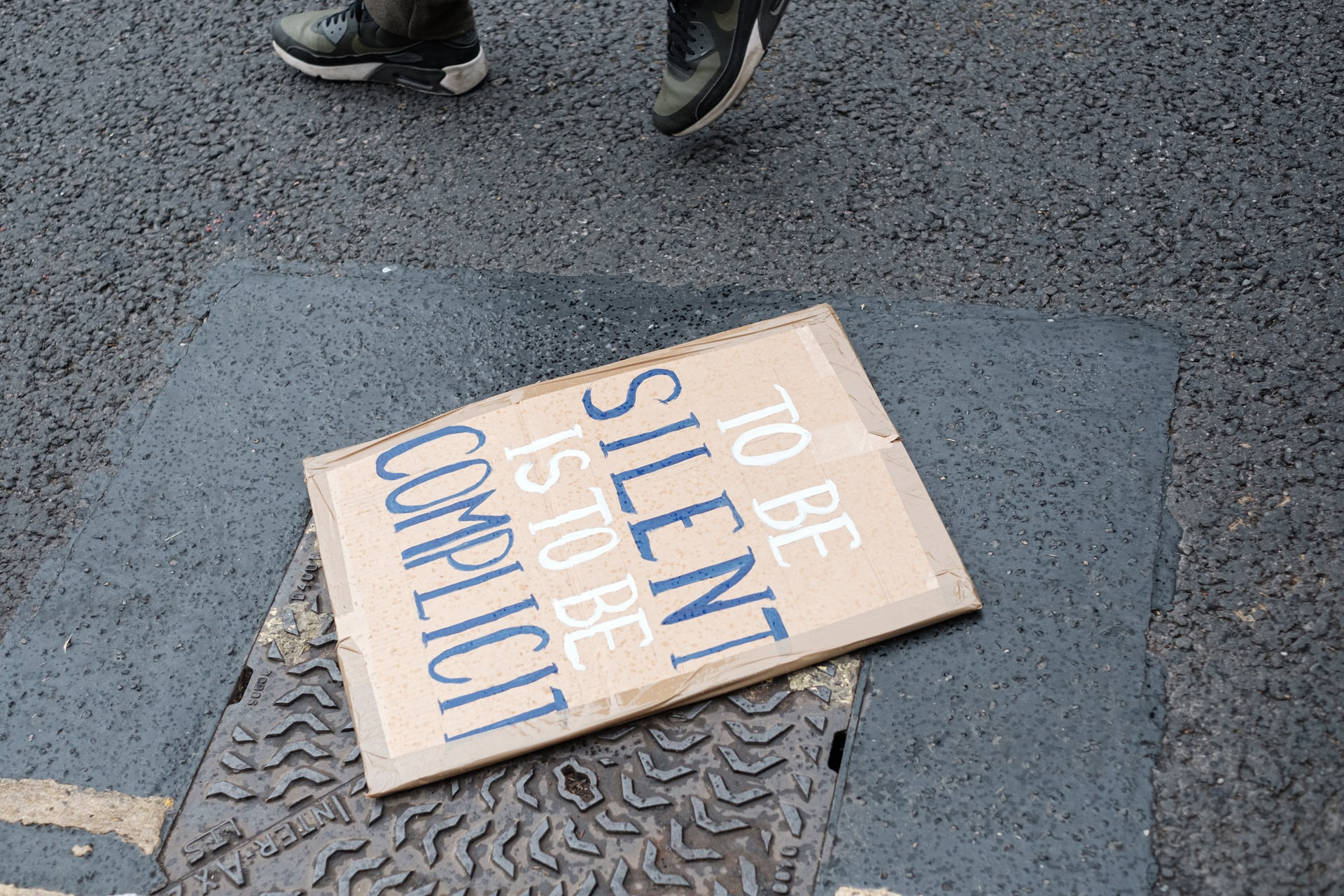 """Cardboard sign on ground that reads """"to be silent is to be complicit"""""""