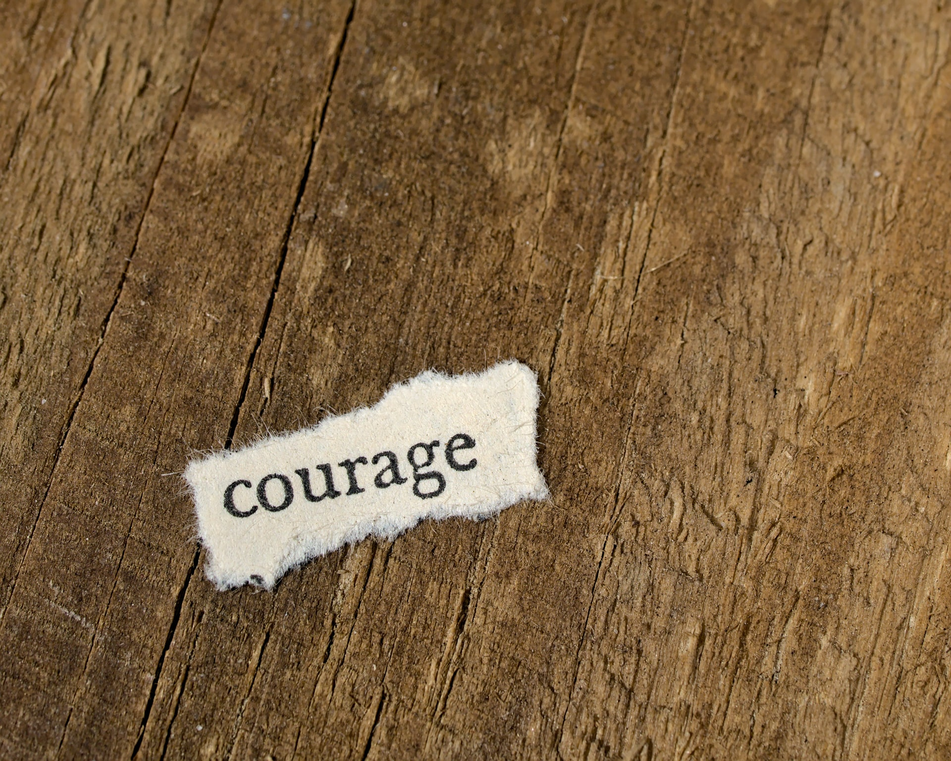 The word courage on scrap of paper on wood